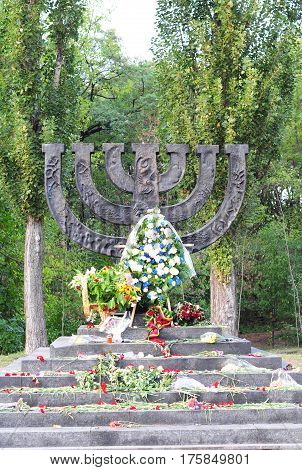 KIEV UKRAINE - March 14 2017: A menorah memorial with flowers dedicated to jewish people executed in 1941 in Babi Yar in Kiev by German forces. Holocaust.
