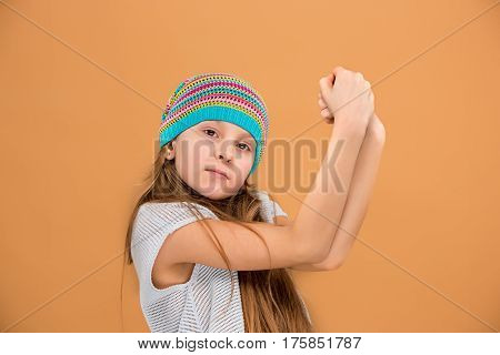 The face of sad teen girl in hat on brown studio background