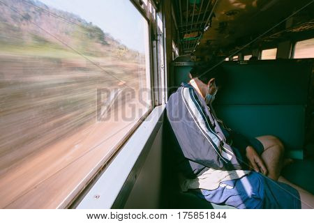 A Man Sleeping Alone On Seat In The Train.