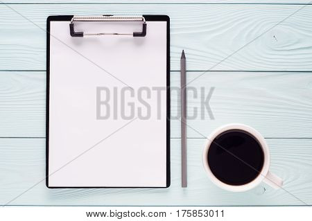 Folder clipboard with white blank paper sheet pencil and cup of coffee with copy space top view. Business concept. Blank clipboard on wooden background flat lay.