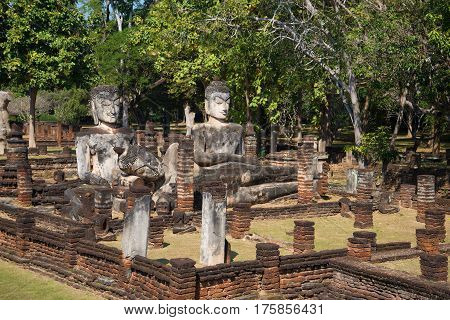Three ancient Buddha sculptures in the ruins of the temple Wat Phra Kaeo. Sunny day. Kamphaeng Phet, Thailand