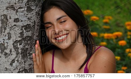 Happy Female Teen Daydreaming Sitting in Park