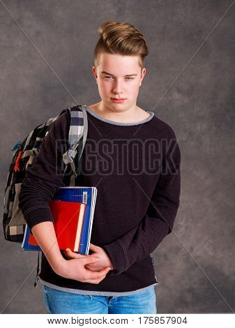 Teenager With Satchel And Books Looking Angry