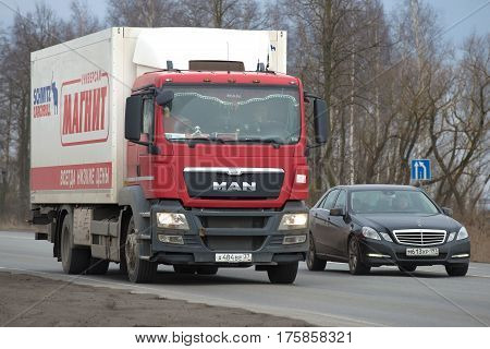 LENINGRAD REGION, RUSSIA - MARCH, 09 2017: Automobile Mercedes overtakes the MAN truck series TGS on the road
