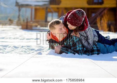 Young couple lies on the snow. Girl climbed onto the back of her boyfriend. Young people look at each other with love and tenderness. Sunny winter day. Good mood.