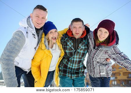 Cheerful group of friends posing for the camera. Two young men and two girl. All good mood. Friends are hugging and laughing merrily.