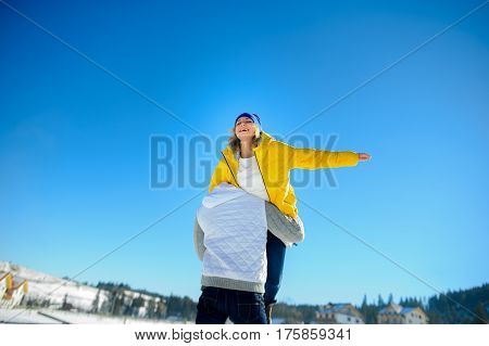 Young man holding in his arms his girlfriend. Man sturdily built easily picks up a fragile girl. Young people having fun. Against the background of the blue sky.