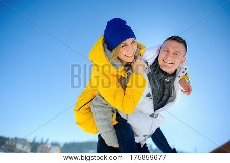 Young man holding his girlfriend on his shoulders. Girl embraces guy for neck. Young people look in the camera and cheerfully laugh. Against the background of the blue sky.