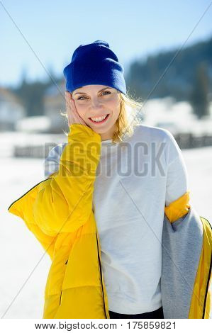 Portrait of the charming young woman. Sunny day blue sky. The woman removes the bright yellow down-padded coat. To her hot and cheerfully.