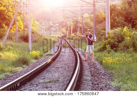 Young Man in Summer Travel Clothing hitch hiking Train on Railroad in wild Forest with Sunlight Background