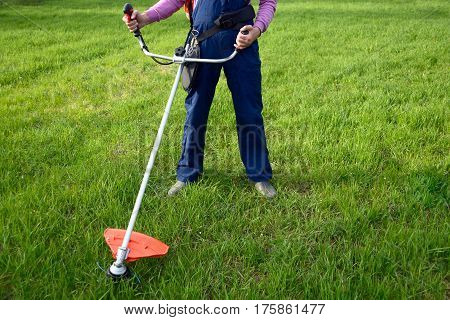 Man mowing grass with petrol weed trimmer