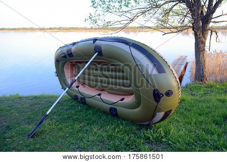Inflatable boat dries leaning on an oar on the river bank