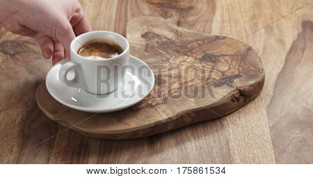 man hand bring espresso on wood table,