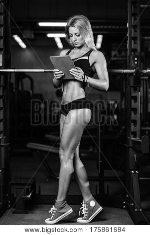 Pretty Fitness Girl With Cellphone In Gym.  Sexy Young Woman