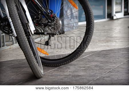 Detail of two modern bicycle wheels on a gray pavement background