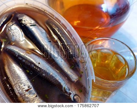 A glass of vodka and bank with spicy salting anchovys. Vodka honey with pepper (Home tincture fortress 45 degrees). Decanter with vodka (tincture). Closeup. Natural food. Traditional Russian cuisine.