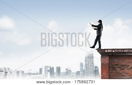 Businessman with blindfolder on eyes walking on building top
