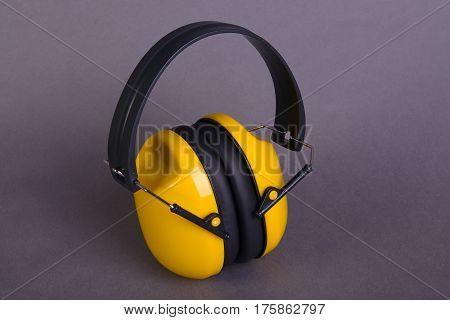 The yellow ear muffs on gray background