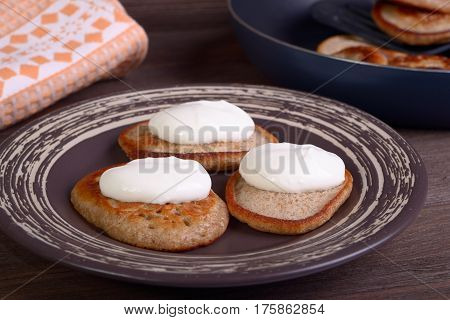 Fritters with sour cream on a plate on a wooden background