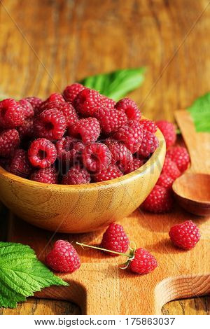 Ripe fresh raspberry in wooden bowl on table