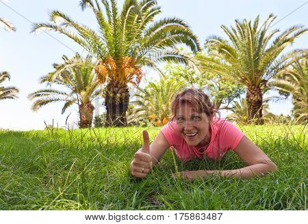 Happy Woman On A Grass In Orchard With Palm Trees