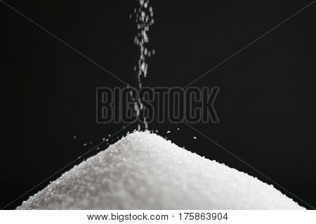 extra small salt crystals fall on black background, time concept