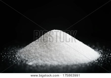 heap of extra small salt on black background, shallow focus
