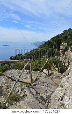 Wooden fence railing and stone pathway along Italy's Amalfi Coast.