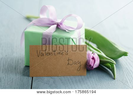 green gift box with purple bow and tulip on blue wood background with valentines day greeting card, romantic photo