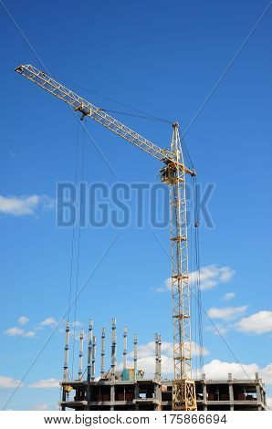 Tower Crane and building construction site with contractor on the top. Industrial building.