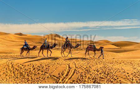 Merzouga, Morocco - February 8, 2017: Tourists riding camels at Erg Chebbi near Merzouga. Sahara, Africa
