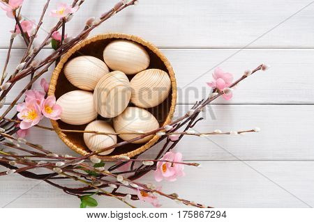 Wooden easter eggs unpainted, mockup for your colors, in basket over white wood background decorated with spring flowers. Top view with copy space