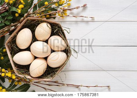 Wooden easter eggs unpainted, mockup for your colors, in basket over white wood background decorated with mimosa and pussy willow spring flowers. Top view with copy space