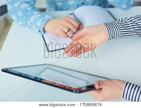 Business woman showing blank no-name tablet pc monitor with copyspace area for slogan or text message to his colleague.
