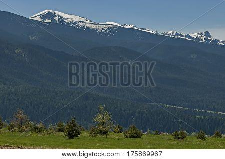 Scene with mountain top, valley and residential district of bulgarian village, Govedartsi, Rila mountain, Bulgaria