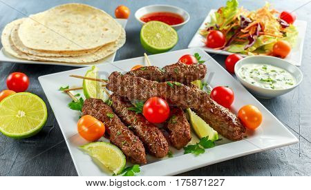 Homemade Kofta kebabs on skewers with pita, lime, vegetables, sweet chili and yogurt sauce on white plate