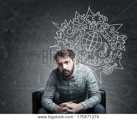 Portrait of a bearded businessman wearing a checkered shirt and sitting near a blackboard with a compliance and regulations sketch drawn on it.