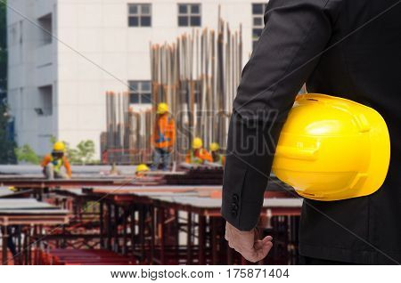 double exposure of businessman hold in hand yellow safety helmet  industrial concept on construction site workers background, color tone effect.