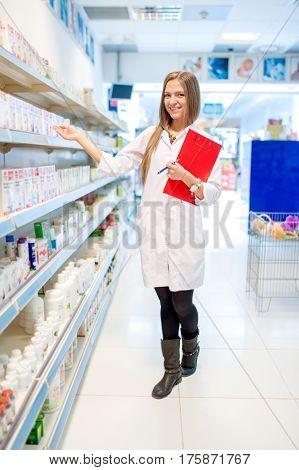 Beautiful Blonde Pharmacist In Drugstore Or Pharmacy Presenting
