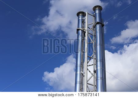 Pipes of shiny metal. Against the background of a high blue sky and clouds