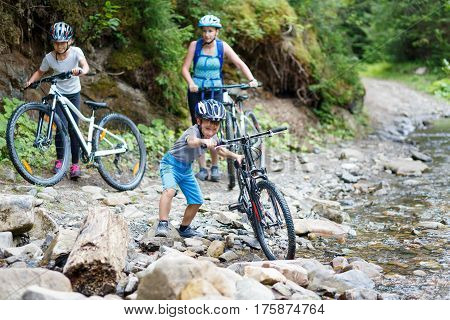 Small boy with his mother and sister on bikes wade the mountain stream