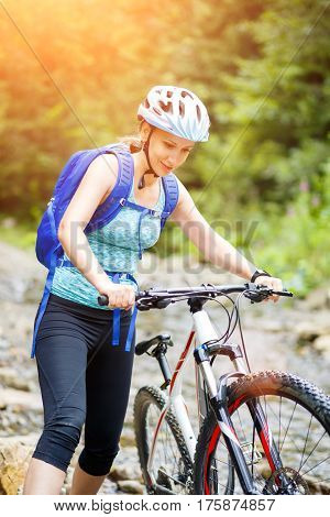 Young smiling woman with bicycle wade the mountain creek on sunny summer day