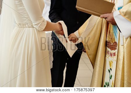 Priest Holding Hands Of Stylish Bride And Elegant Groom At Catholic Wedding Ceremony At Church