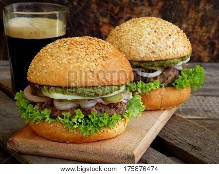 Veggie Burgers With A Chop Of Black Beans, Lettuce, Pickled Onions, Cucumber And A Glass Of Dark Bee