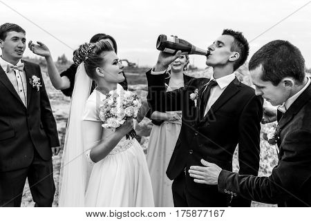 Bride And Groom With Happy Groomsmen And Bridesmaids Having Fun And Toasting With Champagne, Black A