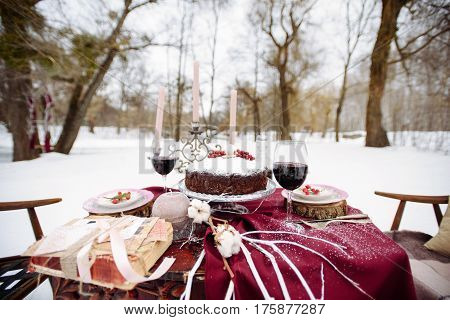 Top view of a table with dread and cookies baskets and candles, two chairs covered with white snow on the background. Picnic in the winter forest