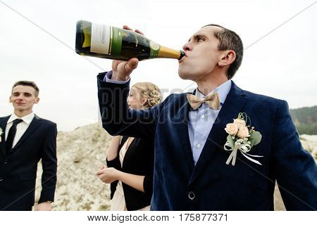 bride and groom with happy groomsmen and bridesmaids having fun and toasting with champagne luxury wedding celebration hilarious moment