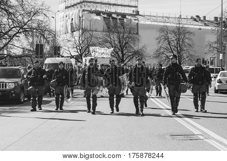 MILAN ITALY - MARCH 8: Policemen follow the secondary school students while taking part in a march to celebrate the International Women's Day on MARCH 8 2017 in Milan.