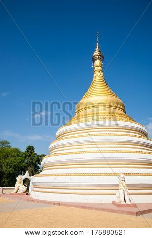 A white and golden round stupa near the Bagaya monastery of the ancient site of Inwa or Ava in the Mandalay region Burma