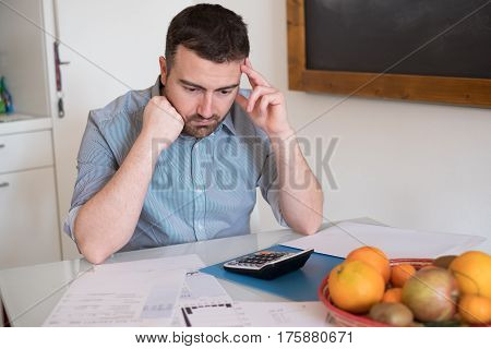 Frustrated Man Calculating Bills And Taxes  Expenses